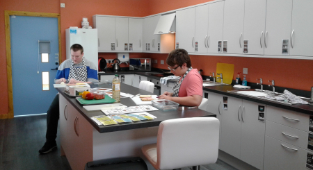 Two young people work in the brand new Life Skills Room at New Struan School