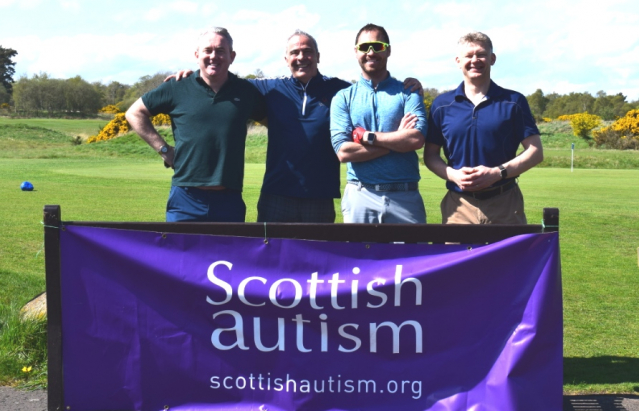 Four men after a game of golf, standing smiling behind a Scottish Autism purple banner
