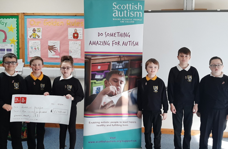 Six children smile while holding a giant cheque for Scottish Autism
