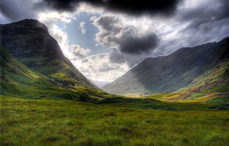 Scottish Highland landscape of Glencoe valley with sun shining through dark clouds
