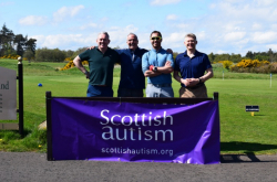 Four golfers smile for the camera while standing behind a purple Scottish Autism banner