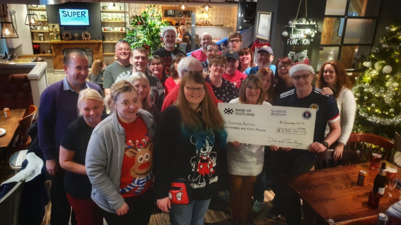A group of people supporting Scottish Autism, attend a Christmas party and hold a cheque for a donation received fromy the Dunfermline Tartan Army