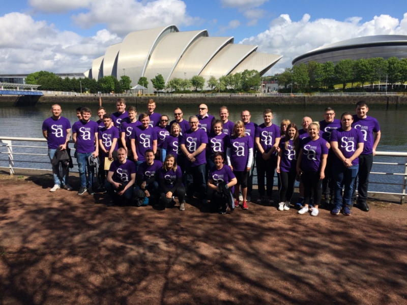 Group of supporters in Scottish Autism purple t-shirts, stand by the River Clyde with the SEC Armadillo in the background