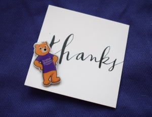 White square wedding favour card with 'Thanks', with metal pin badge of Scottish Autism mascot, Wallace the Bear